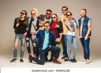 Group of happy young friends in blue jeans smiling at the camera against gray background.