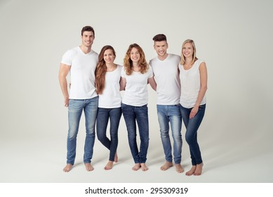 Group of Happy Young Friends in Casual Plain White Shirts and Blue Jeans Smiling at the Camera Against White Background.