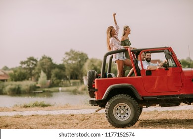Group of happy young friends having fun in convertible car at vacation by river