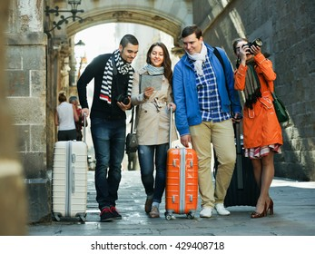 Group of happy young friends with luggage checking direction in map