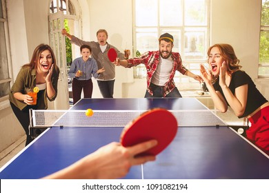 Group of happy young friends playing ping pong table tennis at office or any room. Concept of healthy sport and genuine emotions. Lifestyle, rest concepts