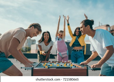 group of happy young friends playing table football on roof