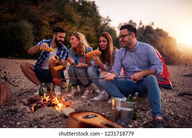 Group of happy young friends relaxing and enjoying summer evening on the beach.