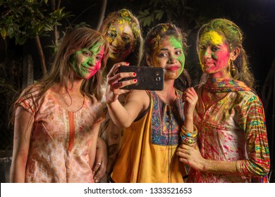 Group of happy young girls having fun and taking selfie using smartphone on Holi festival. Festival and technology concept