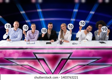 Group Of Happy Young Judges Giving Perfect Scores