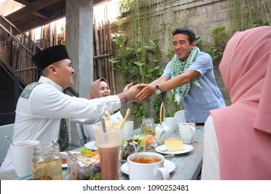 Group happy young muslim embracing each others in dining table during ramadan celebration