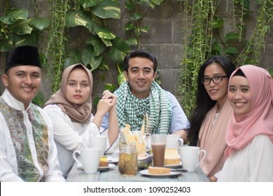 group of happy young muslim having dinner outdoor looking to camera during ramadan celebration, break fasting