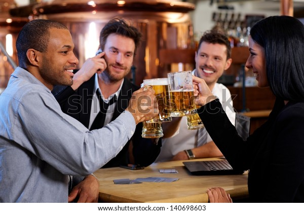 Group of happy young office workers clinking with beer at pub, looking at each other, smiling.