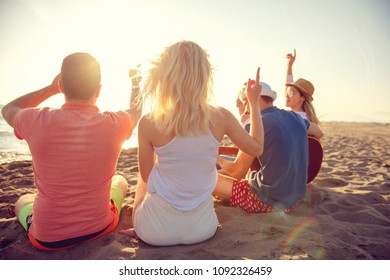 group of happy young people dancing at the beach on beautiful summer sunset