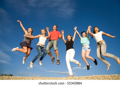 group of happy young people dancing at the beach on  beautiful summer day