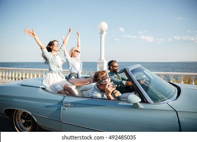 Group of happy young people driving a car