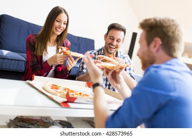 Group of happy young people eating pizza in the room