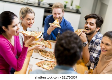 Group of happy young people eating pizza and drinking cider in the modern interior