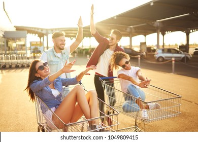 Group of happy young people having fun on shopping trolleys. Multiethnic young people racing on shopping cart. Beautiful summer day with sunlight. Lifestyle concept. Group of  friends enjoy life.