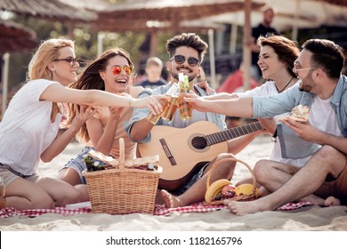 Group of happy young people having a picnic on the beach,drink beer,eat pizza and having fun together.