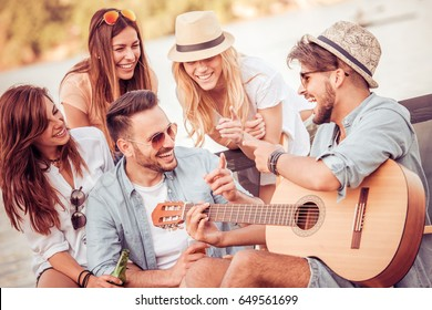 Group of happy young people having a picnic on the beach,having fun together.