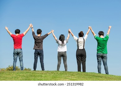 group of happy young people holding hands raised together in park of Bangkok Thailand