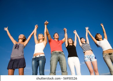group of happy young people holding hands raised together in the sky