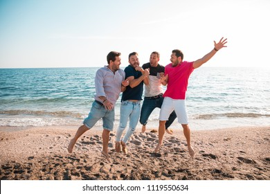 Group of happy young people jumping at the beach on beautiful summer sunset. Four best men friends. Friends and holiday concept