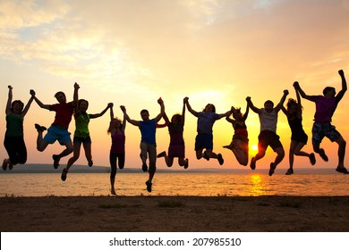group of happy young people jumping at the beach on  beautiful summer sunset