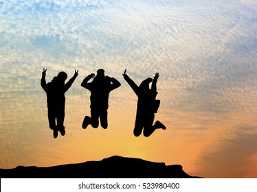 Group of happy young people jumping on the mountain at sunrise