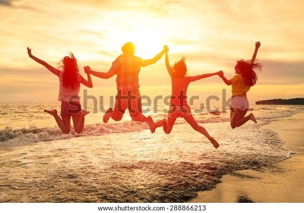 Gruppe glücklicher junger Menschen, die am Strand springen
