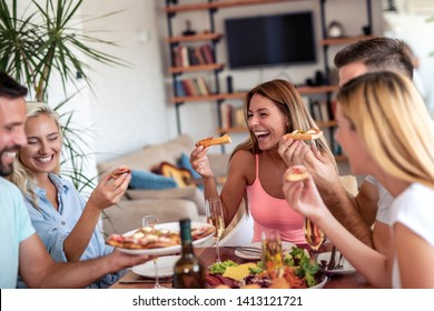 Group of happy young people laugh and chat at dinner table,party for friends at home.