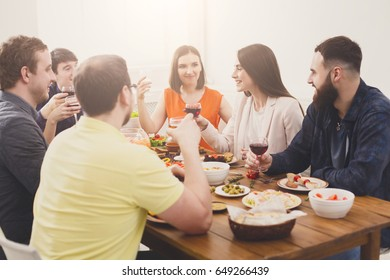 Group of happy young people laugh and chat at dinner table, party for friends indoors at cafe or home. Friendship, relax at holidays and week-end. Men and women sitting at table with various dishes.