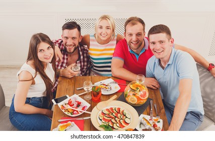 Group of happy young people posing at dinner table, party for friends indoors at cafe or home. Friendship, relax at holidays and week-end. Men and women sitting at table with various dishes.