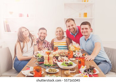 Group of happy young people posing at dinner table, party for friends indoors at cafe or home. Friendship, relax at holidays and week-end. Men and women sitting with various dishes.