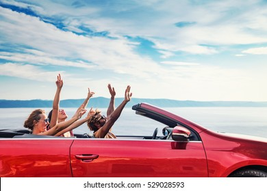 Group of happy young people raising hands to the air in the red convertible.