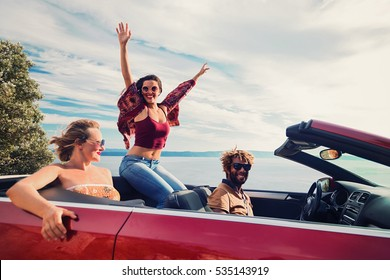 Group of happy young people in the red convertible. Vintage filter applied.