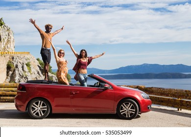Group of happy young people standing in the red convertible car and waving.