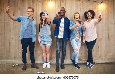Group of happy young people standing against wooden unpainted wall with decorations, all taking selfies with their smartphones, smiling