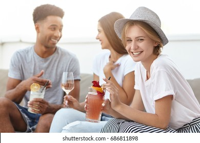 Group of happy young people toasting to love and prosperity, having alcohol drinks at rooftop party. Three cheerful friends enjoying nice time together, having fun at terrace cafe, drinking cocktails