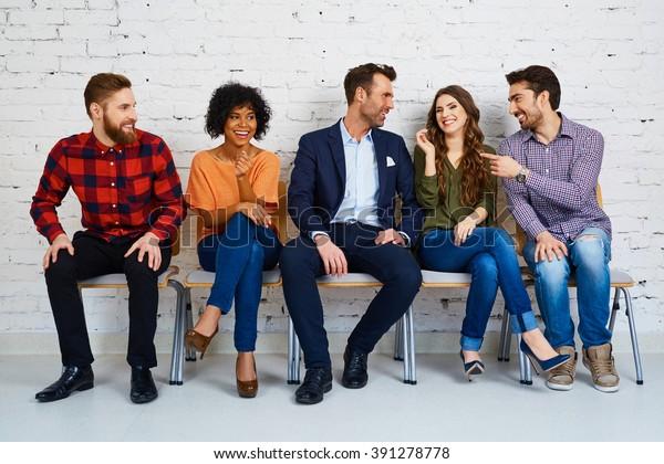 大学で試験を待つ幸せな若者のグループ