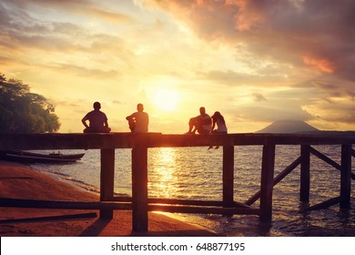 Group of happy young people watching the  beautiful sunrise sitting on the pier.Happiness bliss freedom, travel concept.