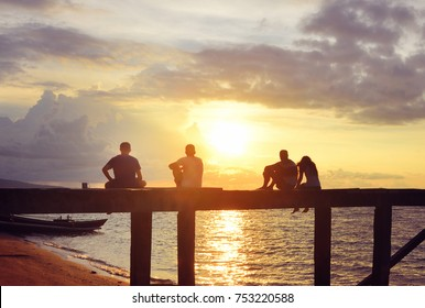 Group of happy young people watching the  beautiful sunrise sitting on the pier