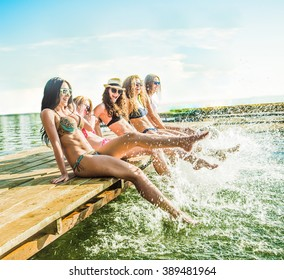 group of happy young woman feet splash water in sea and spraying at the beach on beautiful summer sunset light. Five sexy girls playing on wooden pontoon against blue sky background Enjoy holiday