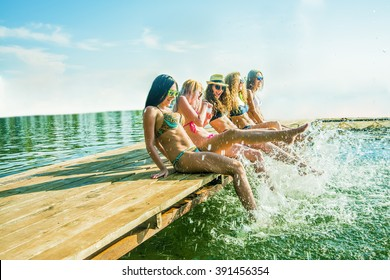 group of happy young woman feet splash water in sea and spraying at the beach on beautiful summer sunset light. Five sexy girls playing on wooden pontoon against blue sky background. Enjoy holiday