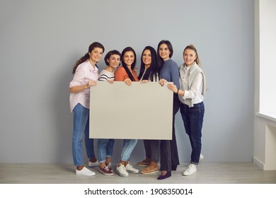 Group of happy young women in their 20s and 30s standing together in office or studio, smiling at camera and holding empty gray cardboard sign, mock-up banner, grey blank poster with space for text