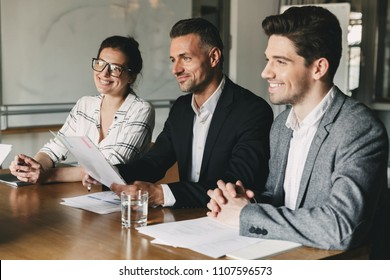 Group of hapy business people in formal suits sitting at table in office and examining resume of new personnel during job interview - business, career and placement concept
