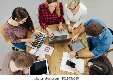 Group of hardworking young businesspeople sitting grouped around a table working on digital devices viewed from overhead