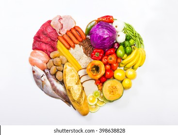 Group of healthy food, the shoot includes protein, carbohydrates, good fats, fruits and vegetables. arranged in the shape of a heart on a plain white surface.