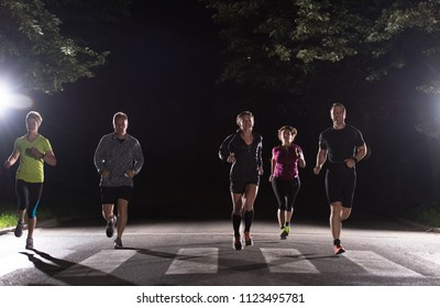 group of healthy people jogging in city park, runners team at night training
