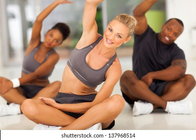group of healthy people stretching at the gym