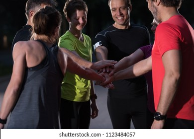 Group of healthy runners giving high five to each other while celebrating success after a training session.