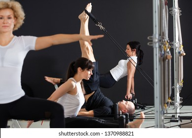 A group of healthy and sporty people practicing Pilates together using Tower reformer,diversity of Pilates poses, The concept of rest after a hard working day
