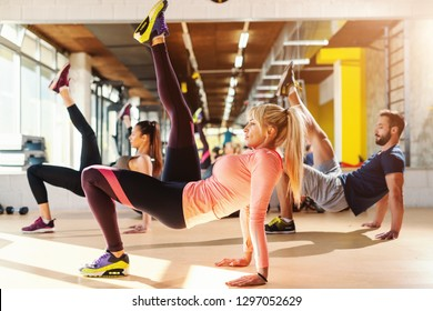 Group of healthy sporty small group of people in sportswear doing front kick exercise on a gym floor. In background mirror.