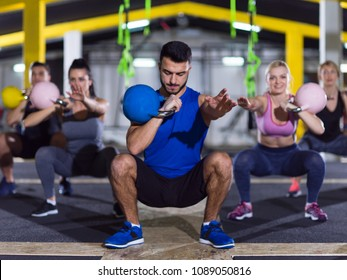 group of healthy young athletes doing exercises with kettlebells at a studio